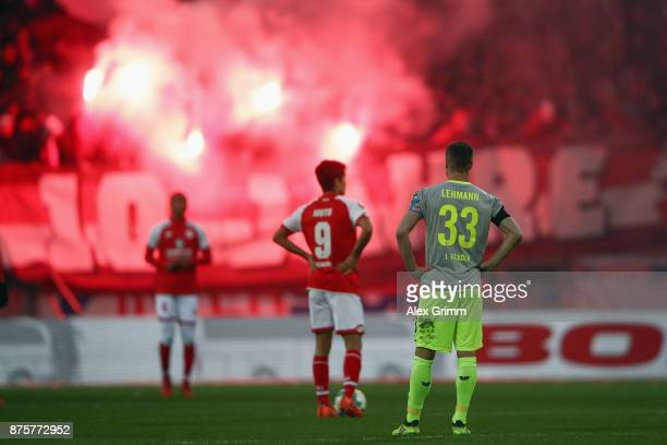Yoshinori Muto of Mainz and Matthias Lehmann of Koeln react as fans of Koeln burn flares during the Bundesliga match between 1 FSV Mainz 05 and 1 FC...