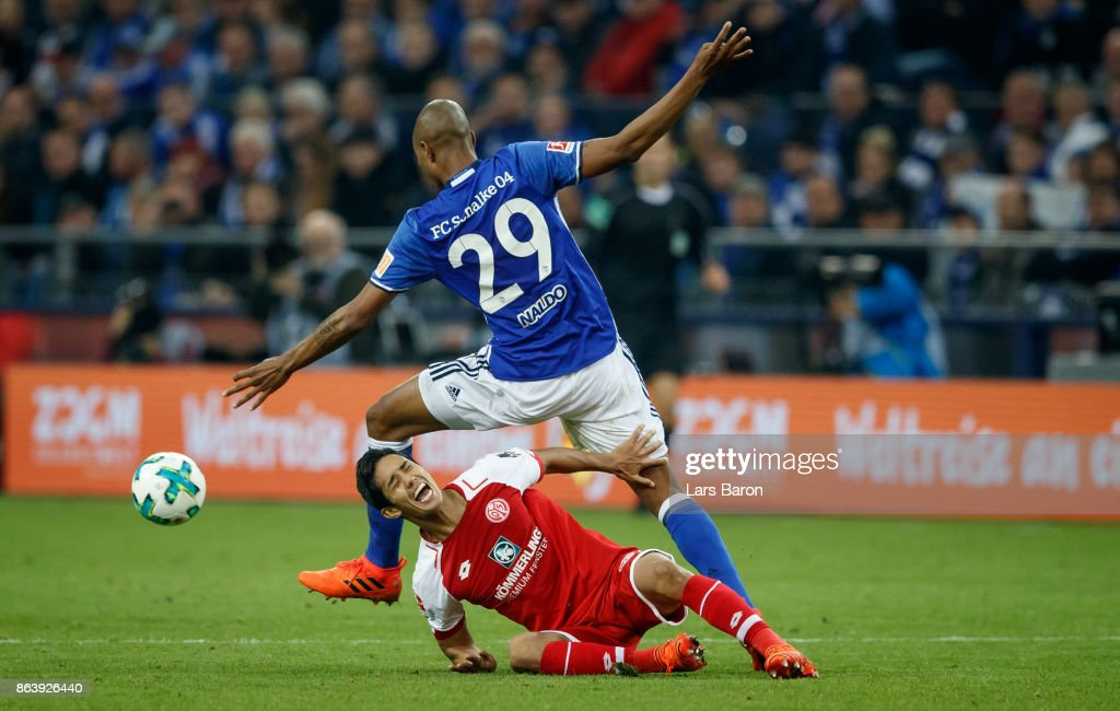 Yoshinori Muto of Mainz is challanged by Naldo of Schalke during the Bundesliga match between FC Schalke 04 and 1. FSV Mainz 05 at Veltins-Arena on October 20, 2017 in Gelsenkirchen, Germany.