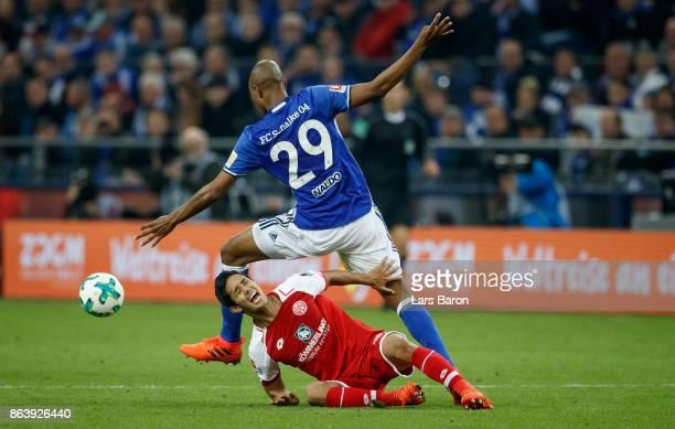 Yoshinori Muto of Mainz is challanged by Naldo of Schalke during the Bundesliga match between FC Schalke 04 and 1 FSV Mainz 05 at VeltinsArena on...