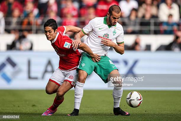 Yoshinori Muto of Mainz is challenged by Alejandro Galvez of Bremen during the Bundesliga match between 1 FSV Mainz 05 and Werder Bremen at Coface...