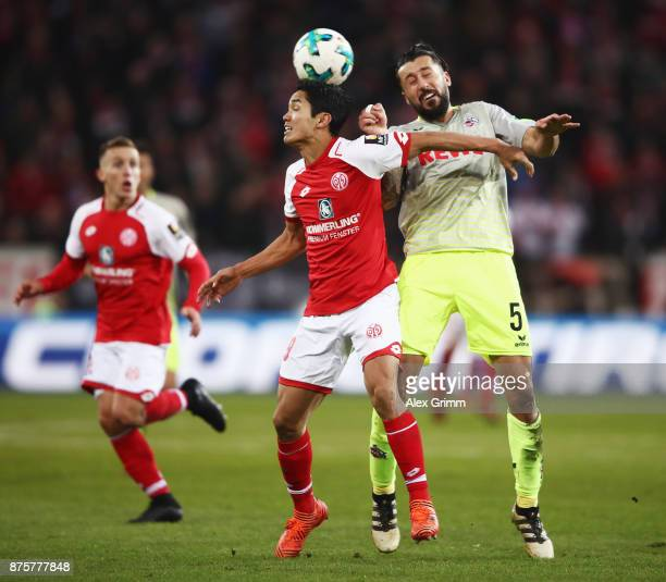 Yoshinori Muto of Mainz is challenged by Dominic Maroh of Koeln during the Bundesliga match between 1 FSV Mainz 05 and 1 FC Koeln at Opel Arena on...