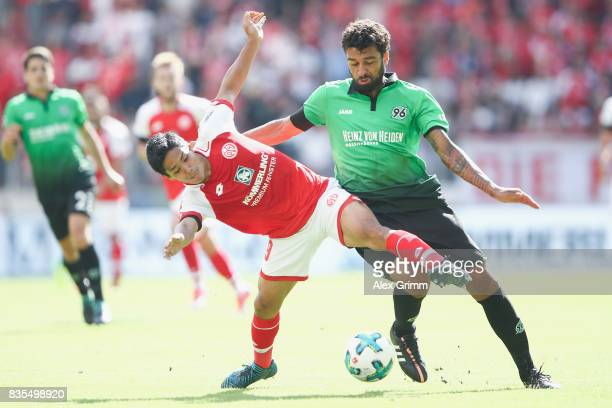 Yoshinori Muto of Mainz is challenged by Felipe of Hannover during the Bundesliga match between 1 FSV Mainz 05 and Hannover 96 at Opel Arena on...