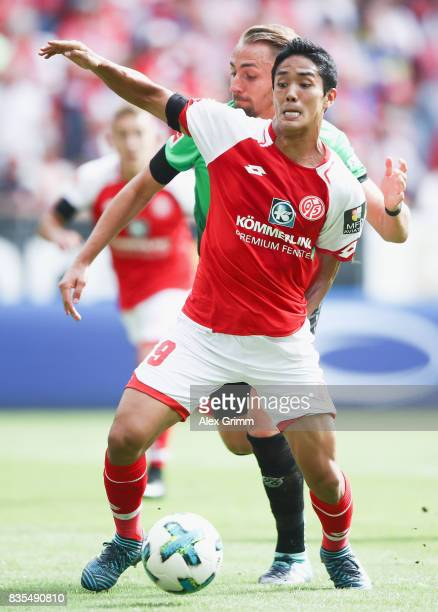 Yoshinori Muto of Mainz is challenged by Florian Huebner of Hannover during the Bundesliga match between 1 FSV Mainz 05 and Hannover 96 at Opel Arena...