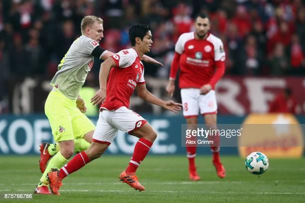 Yoshinori Muto of Mainz is challenged by Frederik Soerensen of Koeln during the Bundesliga match between 1 FSV Mainz 05 and 1 FC Koeln at Opel Arena...