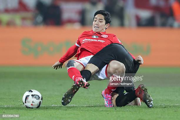 Yoshinori Muto of Mainz is challenged by Jonas Hector of Koeln during the Bundesliga match between 1 FSV Mainz 05 and 1 FC Koeln at Opel Arena on...