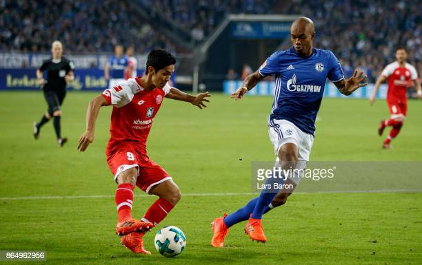 Yoshinori Muto of Mainz is challenged by Naldo of Schalke during the Bundesliga match between FC Schalke 04 and 1 FSV Mainz 05 at VeltinsArena on...