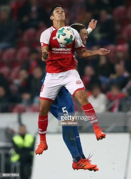 Yoshinori Muto of Mainz is challenged by Rafael Czichos of Kiel during the DFB Cup match between 1 FSV Mainz 05 and Holstein Kiel at Opel Arena on...