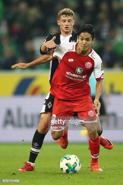 Yoshinori Muto of Mainz runs for the ball with Mickael Cuisance of Moenchengladbach during the Bundesliga match between Borussia Moenchengladbach and...