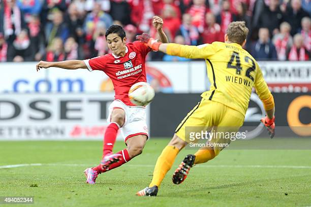 Yoshinori Muto of Mainz scores his team's first goal against goalkeeper Felix Wiedwald of Bremen during the Bundesliga match between 1 FSV Mainz 05...