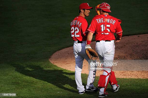 Yoshinori Tateyama of the Texas Rangers talks with catcher Matt Treanor against the Seattle Mariners at Rangers Ballpark on September 24 2011 in...