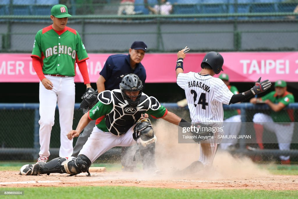 Yoshitaka Nagasawa #24 slides in safe at home, beating the tag of Edcar Pacheco #7 of Mexico in the fifth inning during the Baseball Group B match between Japan and Mexico during the Universiade Taipei at the Xinzhuang Baseball Stadium on August 22, 2017 in Taipei, Taiwan.