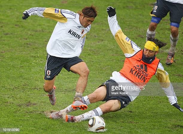 Yoshito Okubo is tackled by a sliding Marcus Tulio Tanaka during a Japan training session at Outeniqua Stadium on June 9 2010 in George South Africa