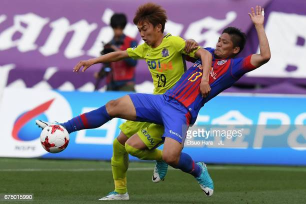 Yoshito Okubo of FC Tokyo and Tsukasa Morishima of Sanfrecce Hiroshima compete for the ball during the JLeague J1 match between FC Tokyo and...