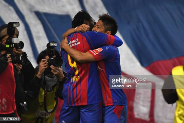 Yoshito Okubo of FC Tokyo celebrates scoring his side's third goal with his team mate Peter Utaka during the JLeague J1 match between FC Tokyo and...