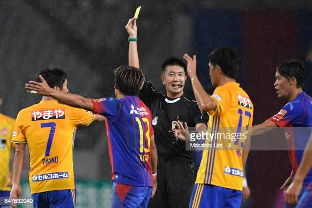 Yoshito Okubo of FC Tokyo is shown a yellow card by referee Kazuyoshi Enomoto during the JLeague J1 match between FC Tokyo and Vegalta Sendai at...
