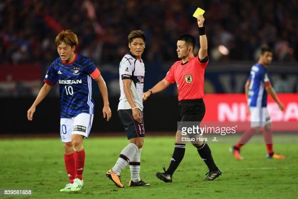Yoshito Okubo of FC Tokyo is shown a yellow card by referee Koichiro Fukushima during the JLeague J1 match between Yokohama FMarinos and FC Tokyo at...