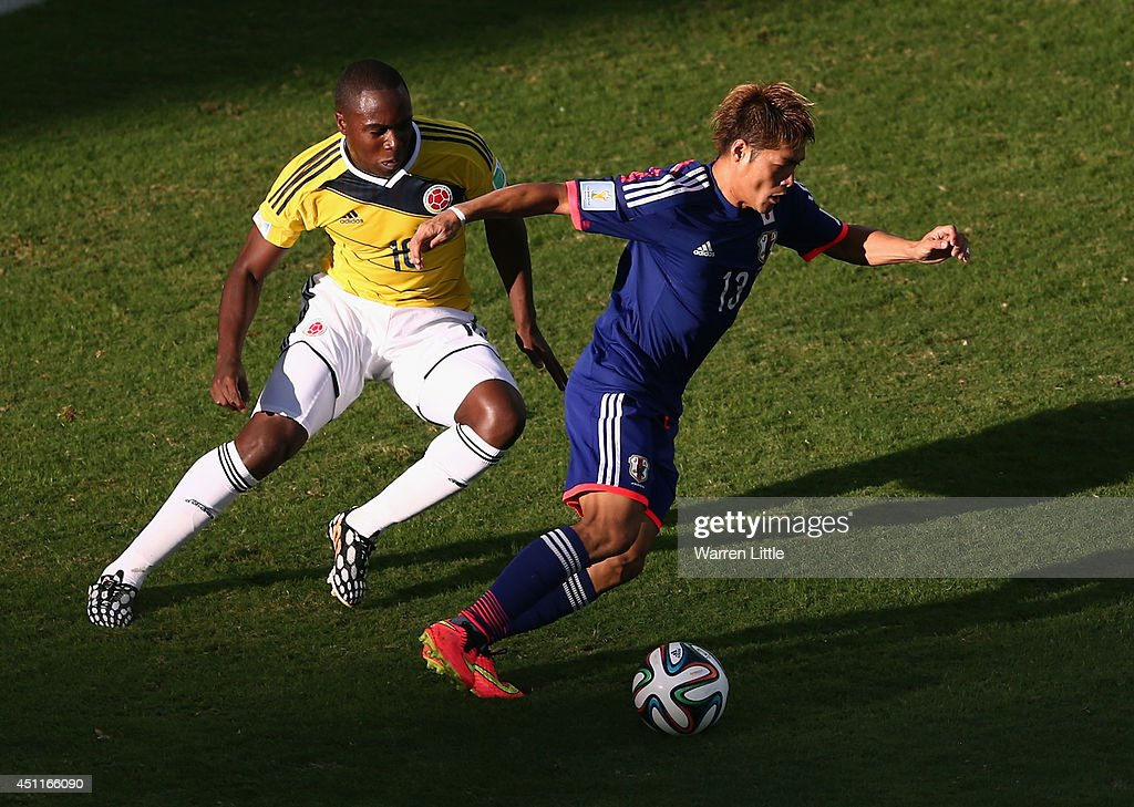 Yoshito Okubo of Japan controls the ball as Eder Alvarez Balanta of Colombia gives chase during the 2014 FIFA World Cup Brazil Group C match between Japan and Colombia at Arena Pantanal on June 24, 2014 in Cuiaba, Brazil.