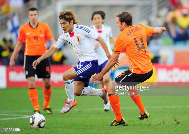 Yoshito Okubo of Japan skips the challeneg of Joris Mathijsen of the Netherlands during the 2010 FIFA World Cup South Africa Group E match between...
