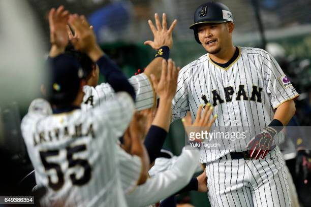 Yoshitomo Tsutsugoh of Team Japan is greeted in the dugout after hitting a tworun Home run in seventh inning during the Game 1 of Pool B against Team...
