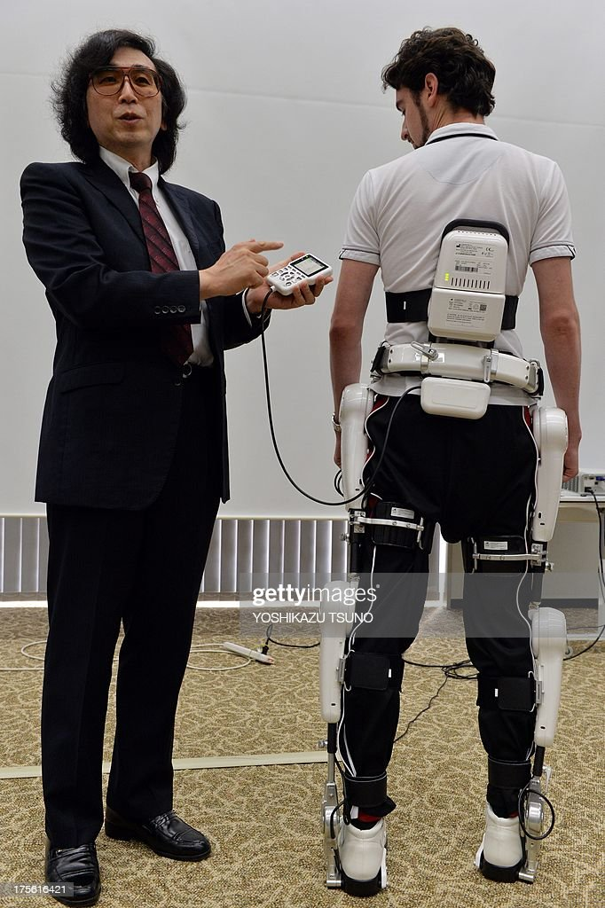 Yoshiyuki Sankai (L), University of Tsukuba professor and president of Japanese robot venture Cyberdyne, displays a new robot suit Hybrid Assistive Limb (HAL) for medical use at the Cyberdyne headquarters in Tsukuba, suburban Tokyo on August 5, 2013. The HAL, which is designed to learn the user's motion and assist their movement, can be used for the rehabilitation of disabled and assist elderly people, was authenticated as a medical device in Europe by European certification authority. AFP PHOTO / Yoshikazu TSUNO