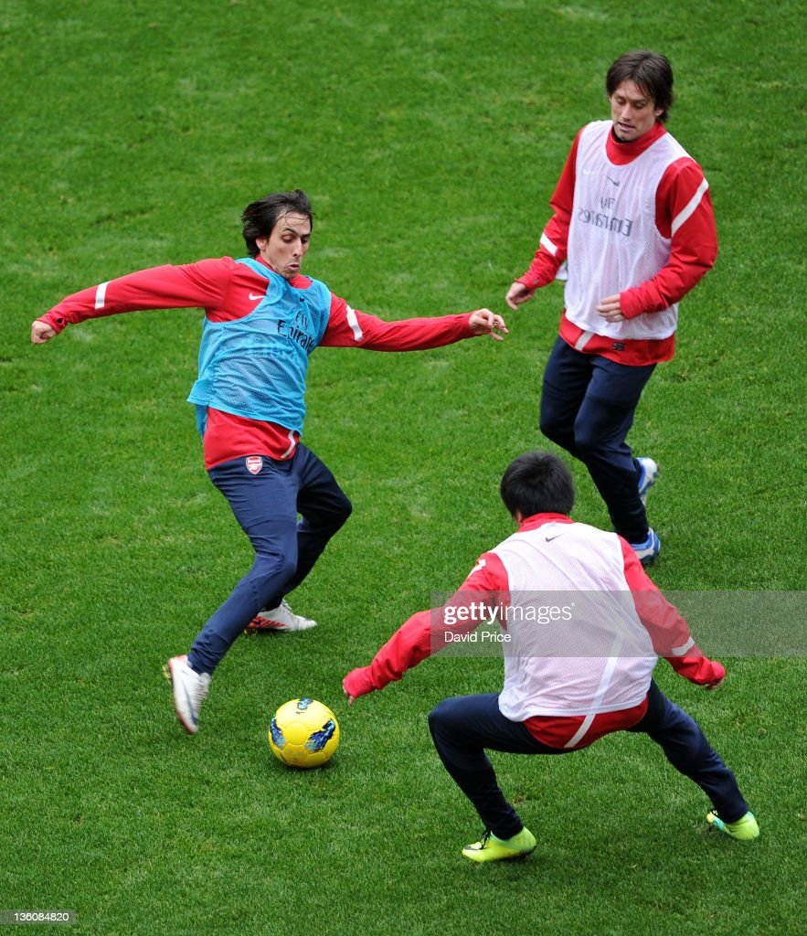 Yossi Benayoun is closed down by Tomas Rosicky and Ryo Miyaichi of Arsenal during a training session at the Emirates Stadium on December 23, 2011 in London, England.