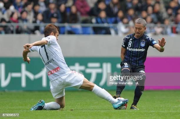 Yosuke Ideguchi of Gamba Osaka and Junichi Inamoto of Consadole Sapporo compete for the ball during the JLeague J1 match between Gamba Osaka and...