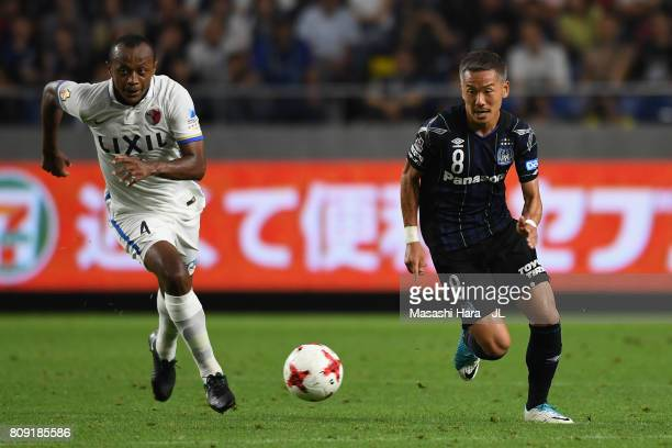 Yosuke Ideguchi of Gamba Osaka and Leo Silva of Kashima Antlers compete for the ball during the JLeague J1 match between Gamba Osaka and Kashima...