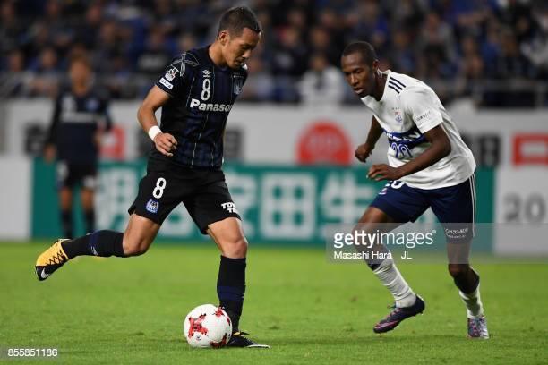 Yosuke Ideguchi of Gamba Osaka and Martinus of Yokohama FMarinos compete for the ball during the JLeague J1 match between Gamba Osaka and Yokohama...