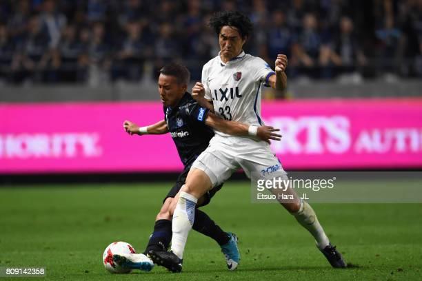 Yosuke Ideguchi of Gamba Osaka and Mu Kanazaki of Kashima Antlers compete for the ball during the JLeague J1 match between Gamba Osaka and Kashima...