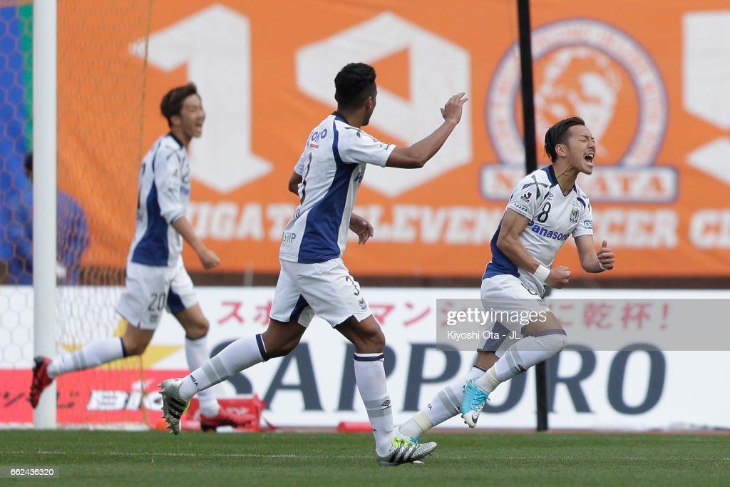 Yosuke Ideguchi (R) of Gamba Osaka celebrates sccoring his side's third goal during the J.League J1 match between Albirex Niigata and Gamba Osaka at Denka Big Swan Stadium on April 1, 2017 in Niigata, Japan.