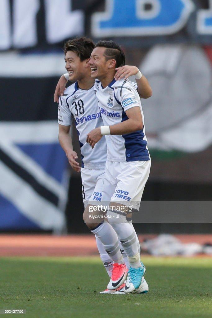Yosuke Ideguchi (R) of Gamba Osaka celebrates sccoring his side's third goal with his team mate Ritsu Doan (L) during the J.League J1 match between Albirex Niigata and Gamba Osaka at Denka Big Swan Stadium on April 1, 2017 in Niigata, Japan.
