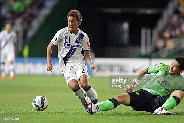 Yosuke Ideguchi of Gamba Osaka compete for the ball with Kim HyungIl of Jeonbuk Hyundai Motors during the AFC Champions League quarter final match...