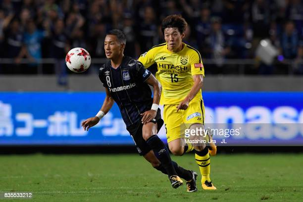 Yosuke Ideguchi of Gamba Osaka controls the ball under pressure of Kim Bo Kyung of Kashiwa Reysol during the JLeague J1 match between Gamba Osaka and...