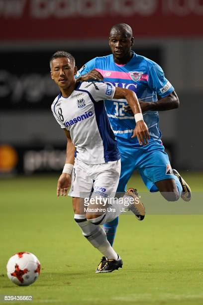 Yosuke Ideguchi of Gamba Osaka controls the ball under pressure of Victor Ibarbo of Sagan Tosu during the JLeague J1 match between Sagan Tosu and...