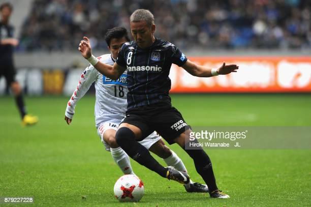 Yosuke Ideguchi of Gamba Osaka controls the ball under pressure of Chanathip Songkrasin of Consadole Sappporo during the JLeague J1 match between...