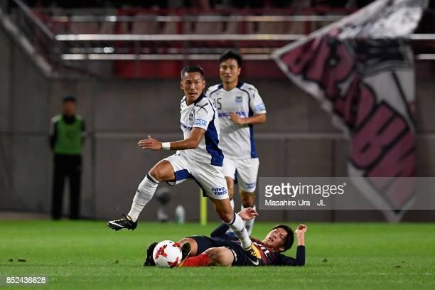 Yosuke Ideguchi of Gamba Osaka goes past Shoma Doi of Kashima Antlers during the JLeague J1 match between Kashima Antlers and Gamba Osaka at Kashima...