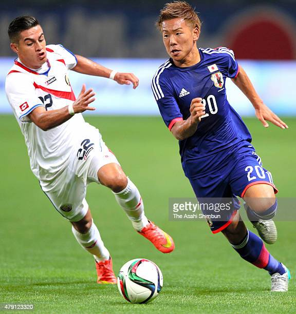 Yosuke Ideguchi of Japan and Ronald Matarrita Ulate of Costa Rica compete for the ball during the international friendly match between U22 Japan and...