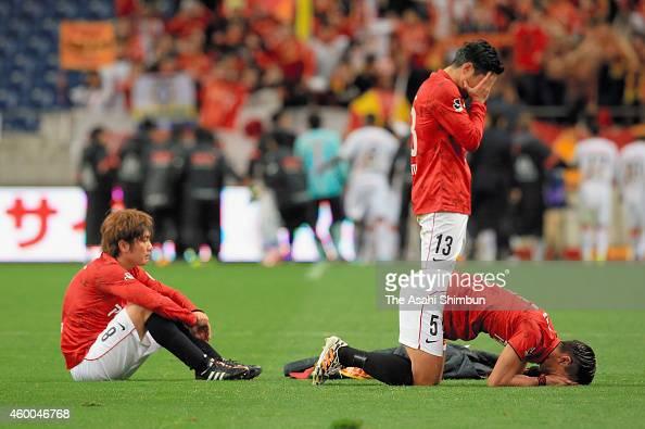 Yosuke Kashiwagi Keita Suzuki and Tomoaki Makino of Urawa Red Diamonds show their dejections as they missed the season champion after the 12 defeat...