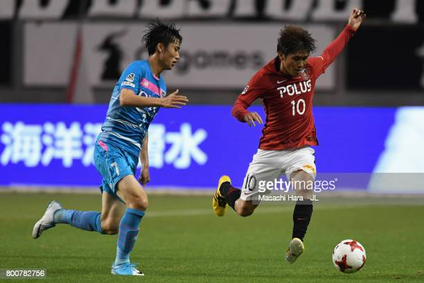 Yosuke Kashiwagi of Urawa Red Diamonds and Daichi Kamada of Sagan Tosu compete for the ball during the JLeague J1 match between Sagan Tosu and Urawa...