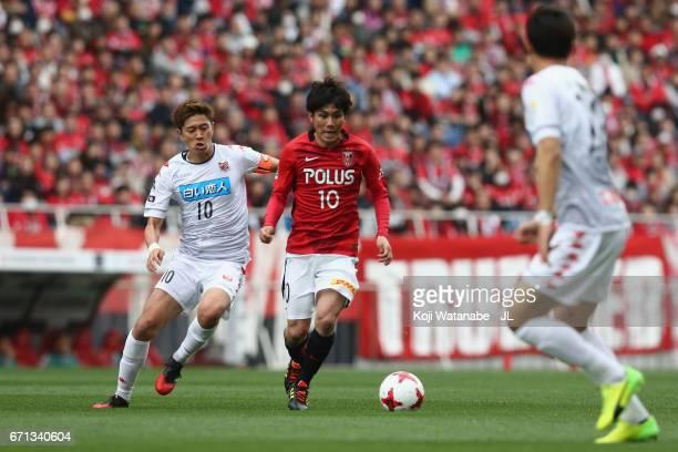 Yosuke Kashiwagi of Urawa Red Diamonds and Hiroki Miyazawa of Consadole Sapporo compete for the ball during the JLeague J1 match between Urawa Red...