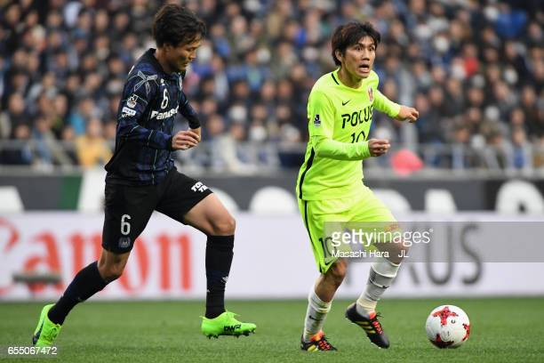 Yosuke Kashiwagi of Urawa Red Diamonds and Kim Jungya of Gamba Osaka compete for the ball during the JLeague J1 match between Gamba Osaka and Urawa...