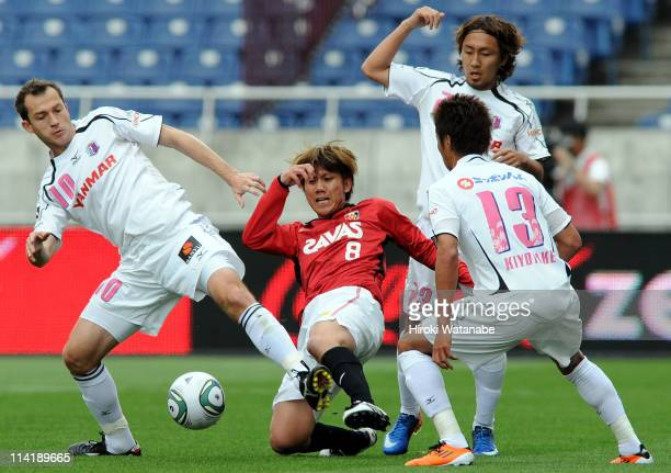 Yosuke Kashiwagi of Urawa Red Diamonds competes for the ball with Martinez Hiroshi Kiyotake and Shu Kurata of Cerezo Osaka during JLeague match...