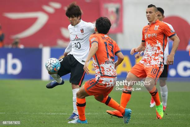 Yosuke Kashiwagi of Urawa Red Diamonds competes for the ball with Chung Woon of Jeju United FC during the AFC Champions League Round of 16 match...