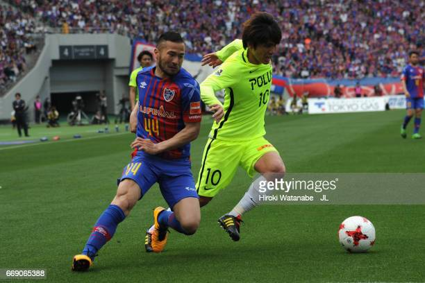 Yosuke Kashiwagi of Urawa Red Diamonds controls the ball under pressure of Takuma Abe of FC Tokyo during the JLeague J1 match between FC Tokyo and...