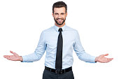 Confident young handsome man in shirt and tie stretching out hands and smiling while standing against white background