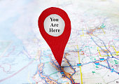 Red locator symbol on a map with You Are Here text