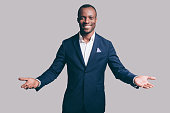 Handsome young African man in smart casual jacket gesturing and smiling while standing against grey background