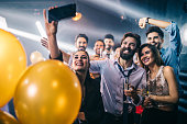 Shot of a group of friends taking selfies on a mobile phone at a party