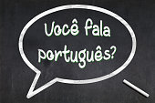 """Blackboard with a bubble drawn in the middle with the short phrase """"Você fala português?"""", meaning """"Do you speak Portuguese ?""""."""