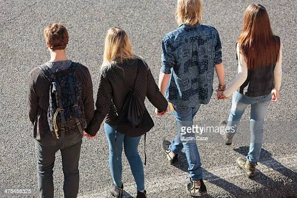 youg people holding hands on the road in the sun